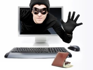 a cyber thief or criminal in a mask peering from the computer screen to scam and steal your identity.